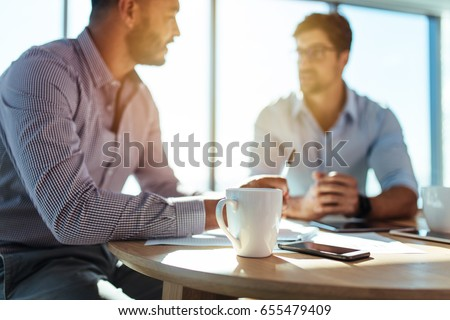 Business executives discussing work at office. Closeup of coffee cup with blurred image of two businessmen sitting on table. Royalty-Free Stock Photo #655479409