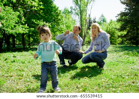 A family of four people are allowed to make soap bubbles. Sunny morning in the spring park. #655539415
