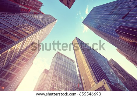 Vintage stylized photo of Manhattan skyscrapers at sunset, looking up perspective, New York City, USA.  #655546693