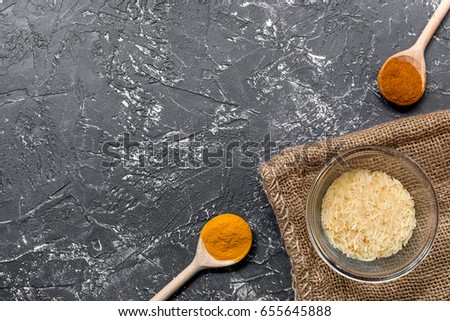 homemade paella ingredients composition with rice in bowl on dark table background top view mock-up #655645888