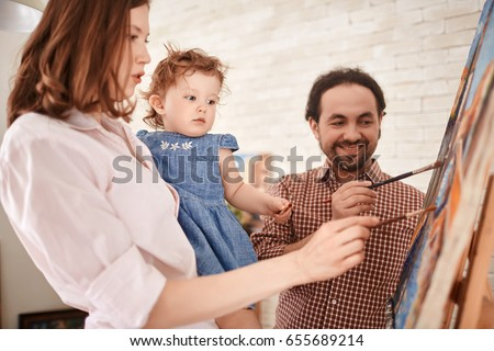 Family of artists working in art studio painting picture on easel together with little girl #655689214