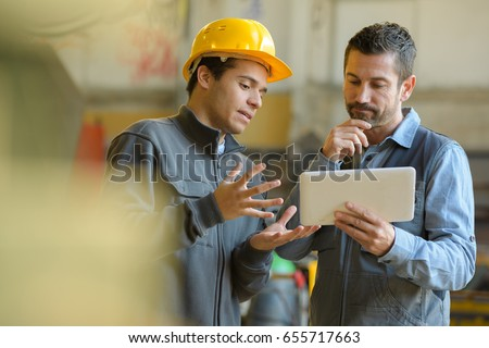 boss and worker checking results on the tablet Royalty-Free Stock Photo #655717663