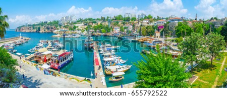 ANTALYA, TURKEY - MAY 6, 2017: Panorama of old marina with numerous yachts and boats, greenery around the embankment, ruins of the city walls, high cliffs, hotels, cafes and bars, on May 6 in Antalya. #655792522