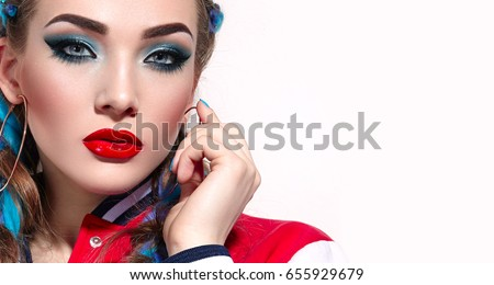 Beautiful fashionable girl with colorful bright blue braids. Bright makeup - blue shadows, red lipstick. Jewelery, bijouterie - earrings, gold rings. Fashion, beauty, care.