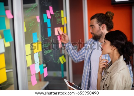 Male and female executives looking at sticky notes in office #655950490