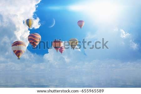Idyllic heavenly picture - colorful hot air balloons flying in blue sky with white clouds and crescent above serene sea