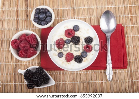 bowl of white yogurt with berries and oat flakes on tablecloth #655992037