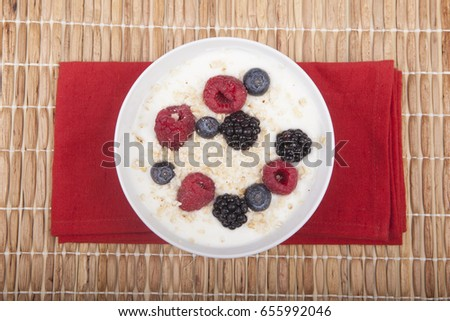 bowl of white yogurt with berries and oat flakes on tablecloth #655992046