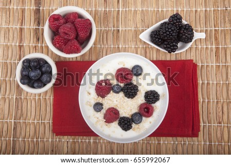 bowl of white yogurt with berries and oat flakes on tablecloth #655992067