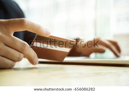 Close-up image of asian business man hands holding credit card and using digital tablet smart phone.Paying with credit card when shopping online. Online shopping concept #656086282