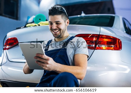 Portrait of a smiling young auto mechanic using digital tablet while leaned on the car. #656106619