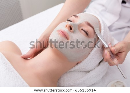 Face peeling mask, spa beauty treatment, skincare. Woman getting facial care by beautician at spa salon, side view, close-up #656135914