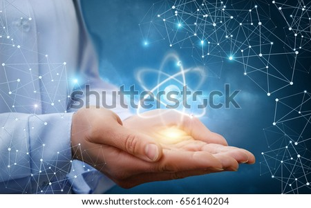 Atom molecule in female hands on a blue background. Royalty-Free Stock Photo #656140204
