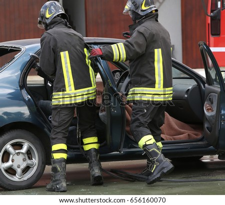Firefighter training to extract trapped man in the car after the road accident #656160070