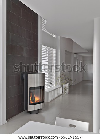 foreground the modern fireplace near to stone wall and the entrance in the modern living area  #656191657
