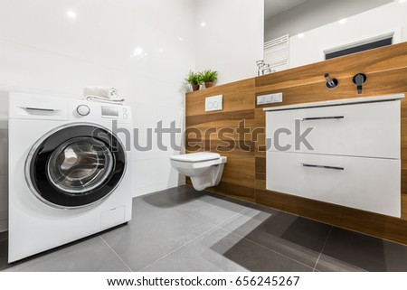 Wooden bathroom with white tiling, washer, cabinet and toilet #656245267