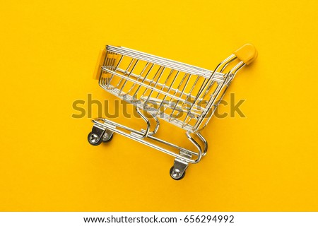 close-up of shopping trolley on yellow background with some copy space #656294992