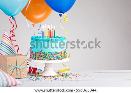 Blue Birthday cake, presents, hats and colorful balloons over light grey. Royalty-Free Stock Photo #656363344