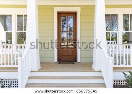 Front door, front view an inviting house with a porch Royalty-Free Stock Photo #656375845