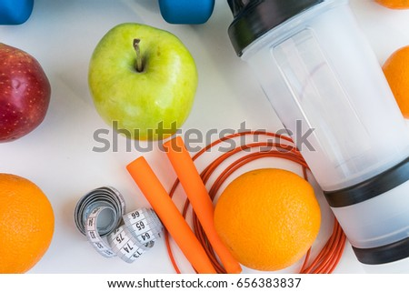 healthy eating concept. Dumbbells, skipping rope, shaker, bananas, oranges, measuring tape waist, oranges, red apple, green apple, orange juice on a white table. healthy lifestyle. sport. #656383837