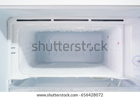 empty freezer of a refrigerator - Ice buildup on the inside of a freezer walls.  #656428072