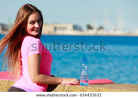 Health and body care idea. Sporty fit attractive woman with bottle of water after exercising workout outdoor. #656433631