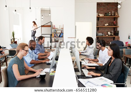 Business colleagues working at a busy open plan office #656511280