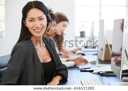 Young Asian woman with headset smiling to camera in office #656511283