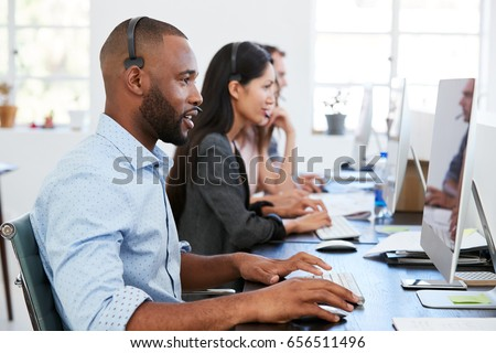 Young black man with headset working at computer in office #656511496