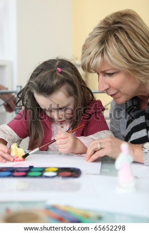 Senior woman making watercolors with a girl #65652298