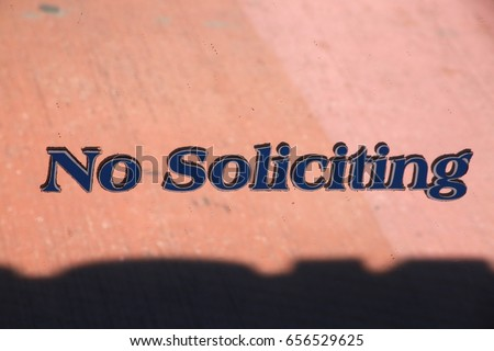 No Soliciting in Purple Letters with Black Border Embedded in Glass Window of Shoppe in Strip Mall Plaza Reflecting Pink Walkway #656529625