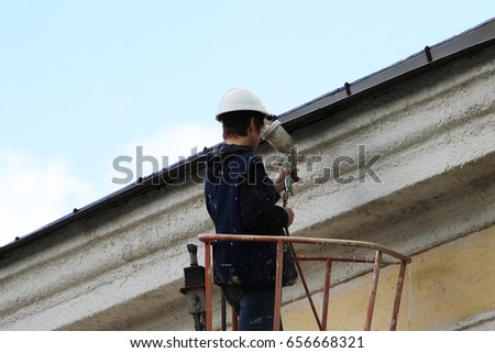 A young worker painter paints the white line of the wall of the building of the city railways station at the height with the help of a lift. #656668321