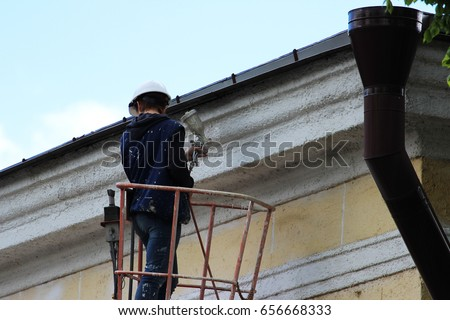 A young worker painter paints the white line of the wall of the building of the city railways station at the height with the help of a lift. #656668333