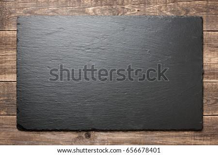 Slate blackboard on wooden background #656678401