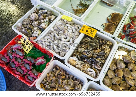GUANGZHOU, CHINA - MARCH 31, 2107: squids and clams on Huangsha Aquatic Product Trading Market in Guangzhou city in spring season. This is the largest fresh water fish market in Southern China #656732455