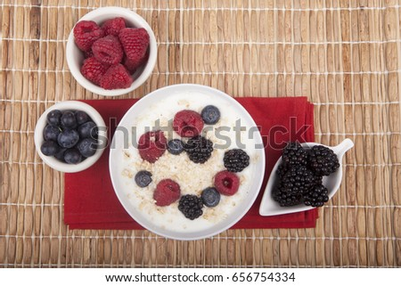 bowl of white yogurt with berries and oat flakes on tablecloth #656754334