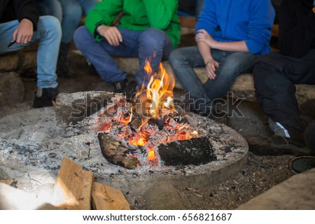 pupils sitting in front of a campfire #656821687