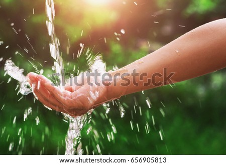 Water pouring splash in hand and nature background with sunshine #656905813