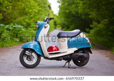Blue retro scooter in the forest with helmet. #656970337