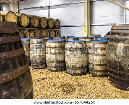 Whisky barrels in warehouse of distillery in Scotland #657044260