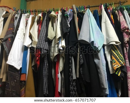 Clothes rack in the room. The clothes rack is a wood. There are many clothes. #657071707