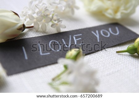 Hand writing title 'I love you' on white background. White roses #657200689