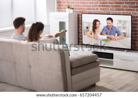 Rear View Of Couple Sitting On Couch Watching Television At Home #657204457
