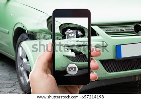Close Up Of A Hand Taking Photo Of Car Accident Through Smartphone