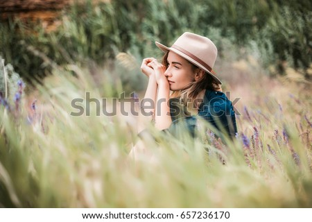 Summer portrait of young hipster woman sitting in a grass on sunny day.young slim beautiful woman,bohemian outfit,indie style, summer vacation,sunny,having fun, positive mood,romantic,woman in hat