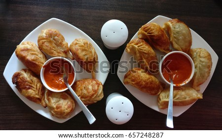 Veg fried cheese momos with sauce in white plates on a wooden table. #657248287