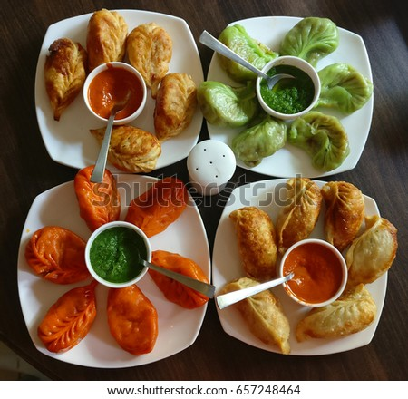 Four plates of Momos | Red Green Yellow momos in four white plates on wooden table #657248464