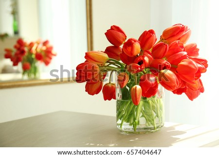 Glass vase with beautiful red tulips in light room #657404647