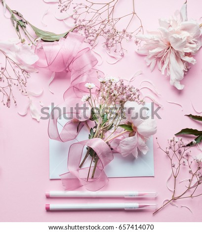 Lovely pink Florist workspace. Beautiful flowers, envelop ,ribbon and markers pencil on pastel background, top view. Creative  Invitation and holiday concept #657414070