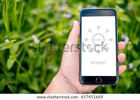 Hands hold smartphone with graphs marketing and cyber technology background. Marketing checking on smartphone. #657451669